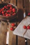 Свежие вишни на плите с обернутым подарком на деревянном столе Стоковые Фото