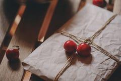 Свежие вишни на плите с обернутым подарком на деревянном столе Стоковая Фотография RF