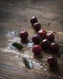 Свежие вишни с водой падают на деревянный стол Стоковые Фотографии RF
