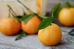 Свежие вкусные tangerines с листьями на деревянном столе Стоковое Изображение RF
