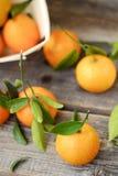 Свежие вкусные tangerines с листьями на деревянном столе Стоковые Изображения RF