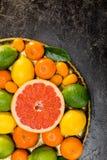 Свежие все цитрусовые фрукты и лист на плите на черноте Стоковые Фотографии RF