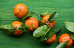 Свежие выбранные Клементины tangerine на деревянной зеленой таблице Стоковые Фотографии RF
