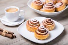 Свежие домодельные плюшки с циннамоном, чашкой кофе, ручками циннамона Стоковые Фотографии RF