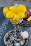 Свежие желтые ветроуловители мороженого персика в стеклянном конусе на пляже, Стоковые Изображения