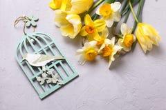 Свежие желтые цветки и декоративная птица на сером текстурированном bac Стоковые Изображения RF