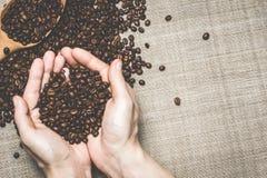 Свежие зажаренные в духовке кофейные зерна придали форму чашки руки в мешковину Стоковое Изображение RF