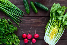 Свежие зеленые овощи (капуста, огурцы), зеленые луки, петрушка и редиска на деревянной предпосылке Стоковое фото RF
