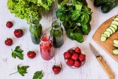 Свежие зеленые smoothies и smoothie клубники с ингридиентами на светлой деревянной предпосылке Здоровые пить вытрезвителя Стоковое фото RF
