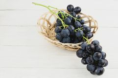 Свежие зрелые голубые виноградины полили из плетеной корзины на старых деревянных белых планках Стоковая Фотография RF