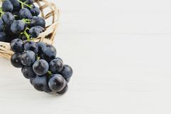 Свежие зрелые голубые виноградины полили из плетеной корзины на старых деревянных белых планках Стоковое фото RF