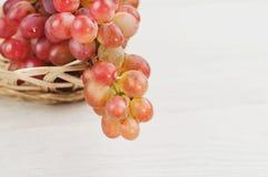 Свежие зрелые розовые виноградины полили из плетеной корзины на старых деревянных белых планках Стоковая Фотография RF