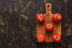 Свежие зрелые томаты на разделочной доске, темная предпосылка, взгляд сверху Экземпляр космоса, плоского положения стоковое фото rf