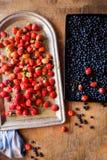 Свежие зрелые ягоды на подносах на деревянной предпосылке, взгляд сверху стоковое фото rf