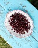 Свежие зрелые вишни в плите на деревянной предпосылке Стоковая Фотография