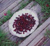 Свежие зрелые вишни в плите на деревянной предпосылке Стоковое Изображение RF