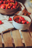 Свежие зрелые вишни на плите с обернутым подарком на деревянном столе Стоковая Фотография