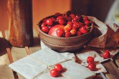 Свежие зрелые вишни на плите с обернутым подарком на деревянном столе Стоковые Изображения RF