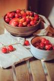 Свежие зрелые вишни на плите с обернутым подарком на деревянном столе Стоковые Изображения