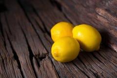 Свежие зрелые лимоны на темной винтажной деревянной предпосылке текстуры стоковые изображения