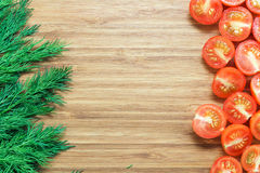 Свежие зрелые красные томаты вишни отрезанные в половинном и свежем зеленом укропе на деревянной разделочной доске Концепция овощ Стоковое Изображение RF