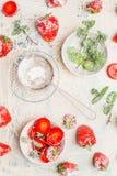 Свежие зрелые клубники с листьями мяты и сахаром замороженности на белой деревянной предпосылке Стоковое Изображение