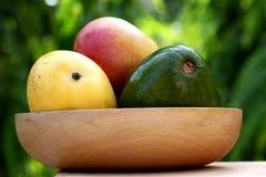 Свежие зрелые манго и авокадо в деревянном шаре Стоковое Изображение RF