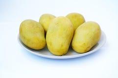 Свежие зрелые манго на белой плите Стоковые Фотографии RF
