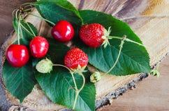 Свежие зрелые органические клубника и вишни на деревянной предпосылке Деревенский тип Стоковое фото RF