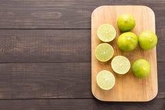 Свежие известки на разделочной доске на деревянной предпосылке Стоковое Фото