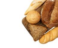Свежие испеченные плюшка и хлеб на разделочной доске изолированной на белизне Стоковое Фото