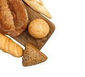 Свежие испеченные плюшка и хлеб на разделочной доске изолированной на белизне Стоковая Фотография RF