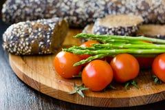 Свежие и зрелые томаты спаржи и вишни с хлебом на деревянной доске Стоковое Фото
