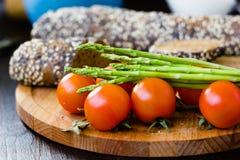 Свежие и зрелые томаты спаржи и вишни с хлебом на деревянной доске Стоковое Изображение RF