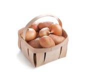 Свежие картошки и шарики лука в деревянной коробке изолированной на wh Стоковое Изображение RF