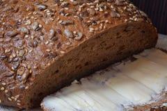 Свежие коричневый хлеб и кусок с маслом Стоковое Изображение