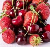 Свежие красивые зрелые ягоды на конце квадрата клубник и вишни белой деревянной предпосылки сладостном вверх Стоковое Изображение