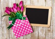 Свежие красивые тюльпаны lila в пакете подарка на деревянной предпосылке Стоковые Изображения RF