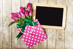 Свежие красивые тюльпаны lila в пакете подарка на деревянной предпосылке Стоковое Изображение RF