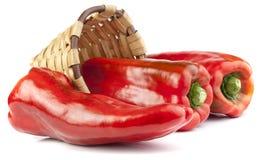 Свежие красные перцы в плетеной корзине стоковые изображения rf