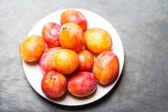 Свежие красные сливы вишни на серой текстурированной каменной предпосылке на wh Стоковые Фото
