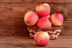 Свежие красные яблоки на деревянном столе и в корзине Предпосылка Брайна деревянная с космосом экземпляра для текста Фото яблок Стоковые Фотографии RF