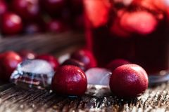 Свежие кубы льда вишен и сок вишни на древесине Стоковые Фото