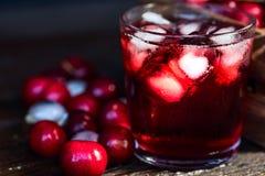Свежие кубы льда вишен и сок вишни на древесине Стоковая Фотография RF