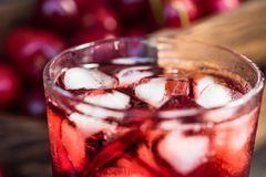 Свежие кубы льда вишен и сок вишни на древесине Стоковые Изображения