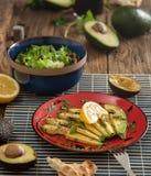 Свежие куски авокадоа на красной плите на старом деревенском деревянном столе Стоковое Фото