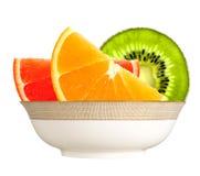 Свежие куски апельсина, кивиа и грейпфрута в плите на wh Стоковая Фотография RF
