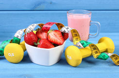 Свежие клубники, milkshake, гантели и сантиметр на голубых досках, концепция здорового и sporty образа жизни Стоковые Изображения RF