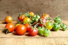 Свежие малые томаты с зеленым стержнем на деревянной предпосылке Стоковая Фотография