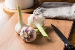 Свежие молодые чеснок и нож на кухонном столе стоковая фотография rf